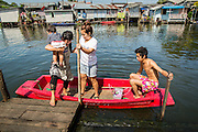 03 JANUARY 2013 - BANGKOK, THAILAND: A family gets out of their canoe in Phra Khanong canal near Wat Mahabut. Just a few minutes from downtown Bangkok, the neighborhoods around Wat Mahabut interlaced with canals, still resemble the Bangkok of 60 years ago. Wat Mahabut is a large temple off Sukhumvit Soi 77. The temple is the site of many shrines to Thai ghosts. Many fortune tellers also work on the temple's grounds.   PHOTO BY JACK KURTZ