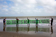Members of Extinction Rebellion take part in an Art Action on Sunny Sands beach on 25th of August 2020 in Folkestone, United Kingdom.  Adults and children walked into the sea fully clothed today with banners and placards to highlight the changing climate crisis we are living in and to highlight sea levels rising. Coincidently climate change was in action at the same time with storm Francis raging with high winds and severe rain.