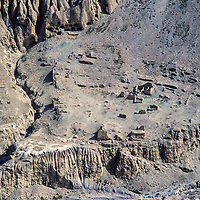 Eroded hills and ruins of a village abandoned after overgrazing and erosion. Note caves from ancienet days.