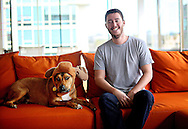 Stephan Goss, CEO of Zeeto Media, sits in his office space with one of several office dogs at heir facility in Downtown San Diego on Friday, December 20, 2013.(Photo by Sandy Huffaker)