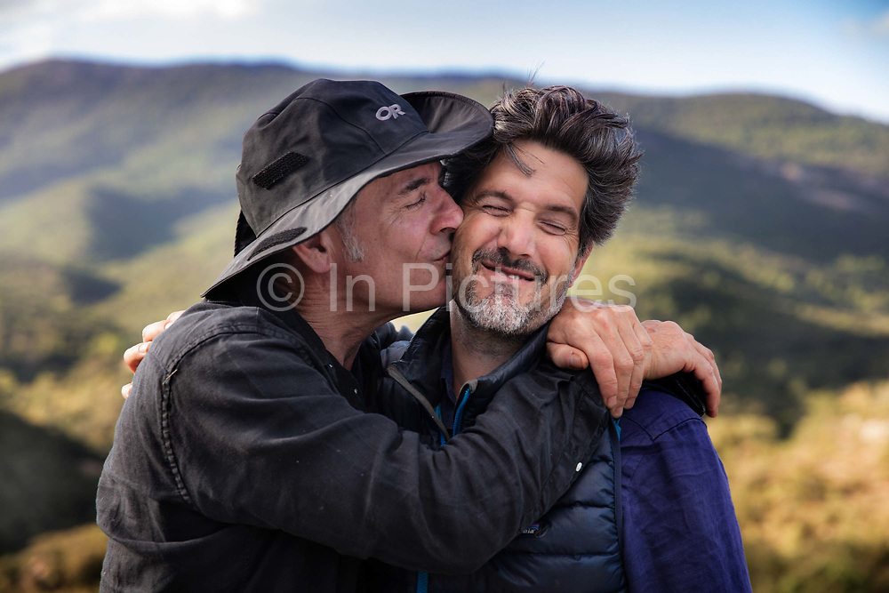 Two male friends having a joking embrace and kiss in the Frence countryside 5th October 2019 near the village of Terme, France. In France the kiss or bissou is an established form of greeting between friends.