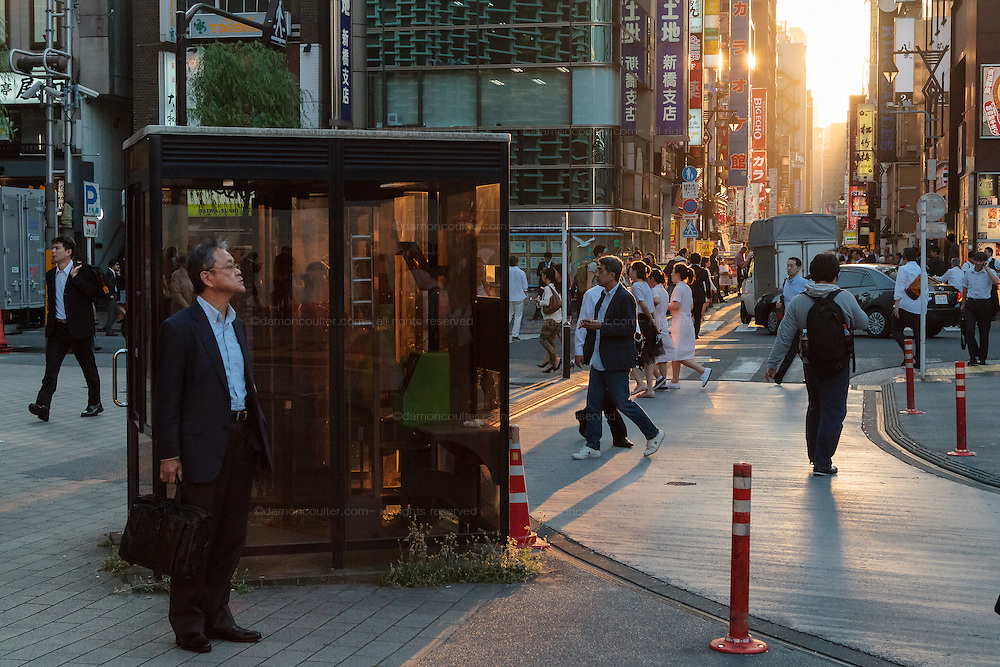A salaryman or male office worker waits by a public telephone booth near the station in Shimbashi at dusk. Shimbashi, Tokyo, Japan. Friday June 3rd 2016