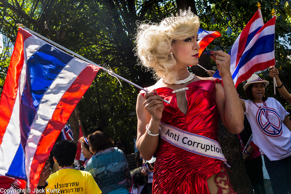 """15 JANUARY 2014 - BANGKOK, THAILAND:  A transvestite supporter of anti-government protest leader Suthep Thaugsuban waits to giver money to Suthep during a protest march in Bangkok. Tens of thousands of Thai anti-government protestors continued to block the streets of Bangkok Wednesday to shut down the Thai capitol. The protest, """"Shutdown Bangkok,"""" is expected to last at least a week. Shutdown Bangkok is organized by People's Democratic Reform Committee (PRDC). It's a continuation of protests that started in early November. There have been shootings almost every night at different protests sites around Bangkok. The malls in Bangkok are still open but many other businesses are closed and mass transit is swamped with both protestors and people who had to use mass transit because the roads were blocked.   PHOTO BY JACK KURTZ"""