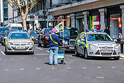 A lone woman tries to block an Oxford Street junction and drivers, including the police, just pass her by - Protestors from Extinction Rebellion block several (Hyde Park, Oxford Cuircus, Piccadilly Circus, Warterloo Bridge and Parliament Square) junctions in London as part of their ongoing protest to demand action by the UK Government on the 'climate chrisis'. The action is part of an international co-ordinated protest.