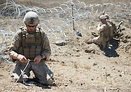 LCpL. Sterr, left, yells to fellow Marines as he untangles the fuse for C-4 explosives during live-fire exercises for the 2nd Battalion, 5th Marine Regiment at Camp Pendleton.