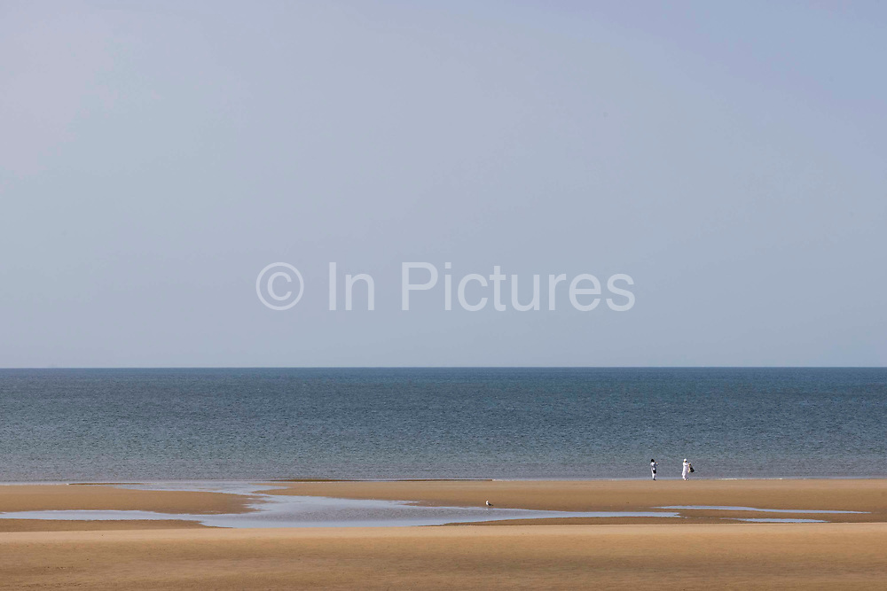 Lone couple on an empty beach during the pandemic on 21st April 2021 in Blackpool, Lancashire, United Kingdom. Blackpool is a large town and seaside resort in the county of Lancashire on the north west coast of England. Blackpool was once a booming resort with it's famous promenade which now, despite having a somewhat shabby appearance, still continues to attract millions of visitors each year. During the coronavirus pandemic however, Blackpool has struggled, with empty streets and closed down businesses creating an atmosphere more like a ghost town.