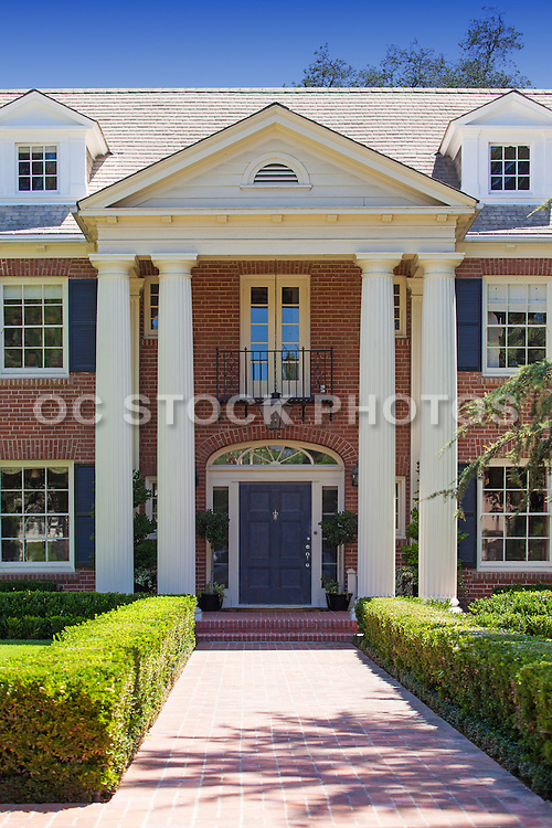Stock Photo of a Front Entry Way of a Colonial Style Home with Red Brick Trim and Black Front Door