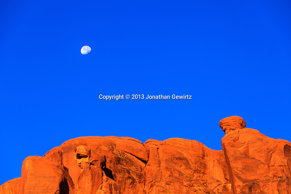 The moon sets over rocky cliffs in Arches National Park, Utah. WATERMARKS WILL NOT APPEAR ON PRINTS OR LICENSED IMAGES.<br /> <br /> Licensing: https://tandemstock.com/assets/44408386