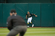 Oakland Athletics right fielder Matt Joyce (23) hits the wall as he makes a catch against the San Francisco Giants at Oakland Coliseum in Oakland, California, on August 1, 2017. (Stan Olszewski/Special to S.F. Examiner)