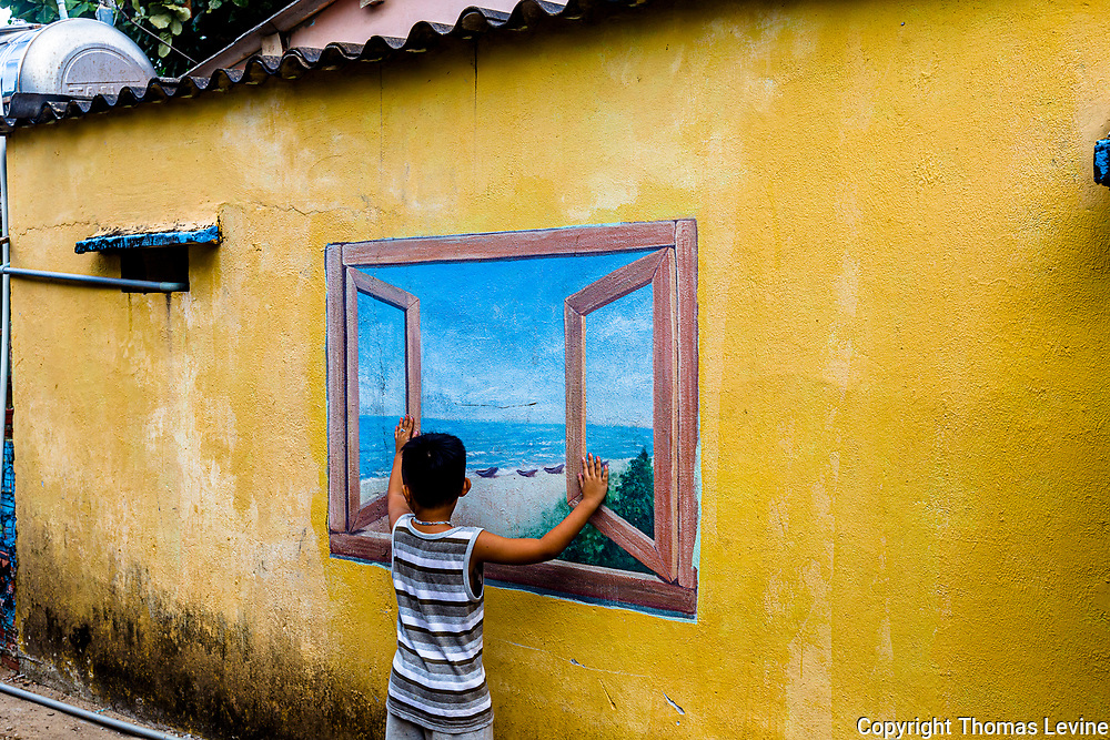 Wall Murals with a real child posing in front of a wall painting.