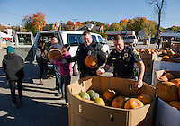 Hyun Choi, Ruth Sterling, Officer Bassett, Lucy Le, Officer Orton and Sergeant Hubbard load up Plymouth Elementary School's van with 100 pumpkins at Vista Foods on Monday morning.  (Karen Bobotas/for the Laconia Daily Sun)