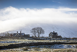 © Licensed to London News Pictures. 10/11/2016. Ingleton UK. Picture shows houses in the shadow of the snow covered Pen-y-ghent mountain in the Yorkshire Dales. Photo credit: Andrew McCaren/LNP