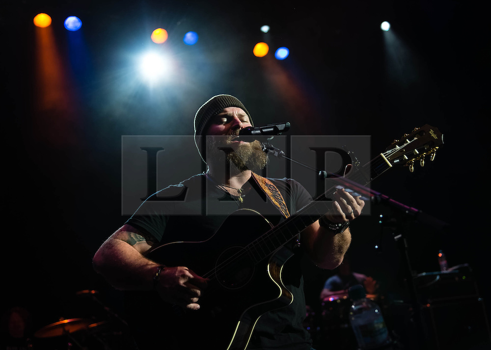 """© Licensed to London News Pictures. 01/07/2013. London, UK.   Zac Brown of Zac Brown Band performing live at Shepherds Bush Empire. Zac Brown Band is Grammy award winning American country/folk band based in Atlanta, Georgia. The lineup consists of Zac Brown (lead vocals, guitar), Jimmy De Martini (fiddle, vocals), John Driskell Hopkins (bass guitar, vocals), Coy Bowles (guitar, keyboards), Chris Fryar (drums), Clay Cook (guitar, keyboards, mandolin, steel guitar, vocals), and Daniel de los Reyes (percussion).  in 2013 the band won a Grammy for Best Country Album with """"Uncaged"""", and since forming they have earned a total of 55 award nominations & won 7 from the Grammys, Academy of Country Music, American Music Awards, Country Music Association and Country Music Television. Photo credit : Richard Isaac/LNP"""