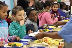 © Licenced to London News Pictures. 04/12/2013. London. UK.  <br /> General view of children being served their lunch in the canteen of Walnut Tree Walk Primary School in London, December 4th 2013. The Deputy Prime Minister Nick Clegg announced in September that one of his key priorities for the Autumn Statement was to provide free school meals to every infant school pupil.<br /> Photo Credit: Susannah Ireland