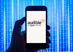 Person holding smart phone with amazon Audible  logo displayed on the screen. EDITORIAL USE ONLY