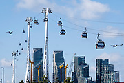 A view of Emirates Air Line cable cars and Thames riverside residential apartment high-rises on the Greenwich Peninsular, on 11th August 2021, in London, England.