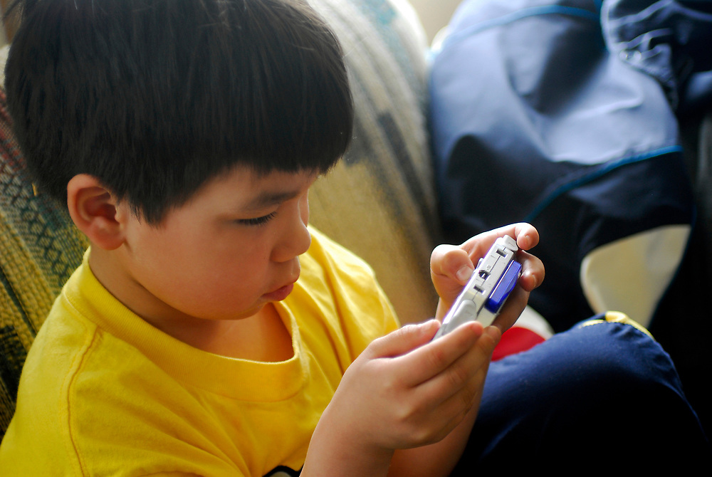Barrow, Alaska. Cortez Leavitt plays with his gameboy. May 2nd 2007. (Model Release)
