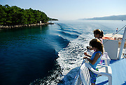 Two children (9 years old and 5 years old) standing on deck of inter-island boat, islands in background. Island of Hvar, Croatia
