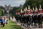 Members of the public watch the Household Cavalry Mounted Regiment proceed along the Long Walk to Windsor Castle for the ceremony of Trooping the Colour to mark the Queens official birthday on 12th June 2021 in Windsor, United Kingdom. A socially distanced and scaled down Trooping the Colour ceremony is taking place this year incorporating many of the elements from the annual ceremonial parade on Horse Guards, with F Company Scots Guards Trooping the Colour of the 2nd Battalion Scots Guards in the Castle Quadrangle.