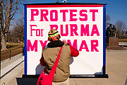 06 MARCH 2021 - DES MOINES, IOWA: A member of the Burmese community in Iowa works on a large sign protesting the military coup in Myanmar. About 300 members of the Burmese community in Iowa gathered at the State Capitol in Des Moines Saturday to protest against the military coup that deposed the popularly elected government of Aung San Suu Kyi and continuing military oppression in Myanmar. There are about 10,000 people in Iowa's Burmese community.            PHOTO BY JACK KURTZ