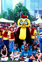 Stock photo of a group of young children posing with a bee mascot at the International Festival in downtown Houston Texas