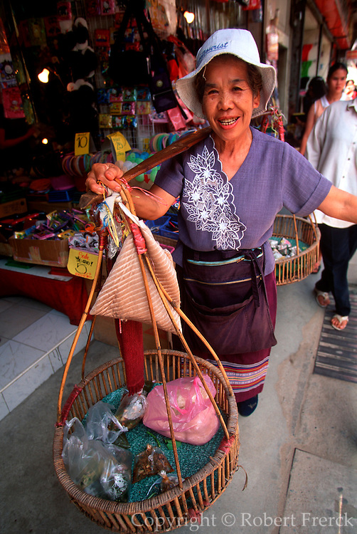 THAILAND, NORTH, GOLDEN TRIANGLE Chiang Mai, woman carrying items using traditional baskets carried across the shoulder