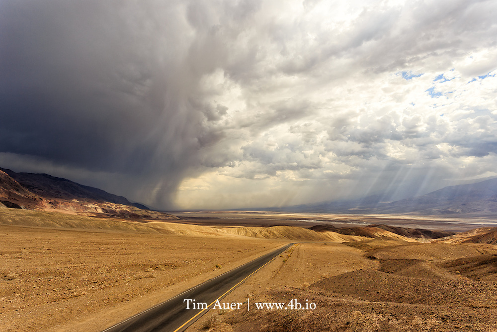 Death Valley, California, USA<br /> A road bisects the clouds that are carrying a relatively uncommon weather phenomenon in Death Valley: rain. <br /> <br /> As expected for Death Valley in July, it was hot, but nothing unusual at about 121F/50C. What was more unusual was the storm that blew in later that day. The storm front came in over the Black Mountains in the southeast and moved northwest up the valley. There were raindrops on the valley floor, lightning high in the mountains, and fierce wind everywhere blowing sand. This photo was taken as the storm crested over the range.  The resulting change in air pressure mixed with extremely hot air lead to violent turbulence and sandstorms, and flash floods in all the washes. <br /> <br /> Death Valley is a world of extremes. As one of the hottest and driest places on the planet, it supports a staggering amount of wildlife, and despite the lack of water, some of its most prominent landscapes are the result of water erosion.  Captured in this photo is evidence of a land shaped by several of the earth's most transformational forces: water erosion, wind erosion, volcanic, and plate tectonics like basin/range extension and earthquake. <br /> <br /> Canon EOS 6D; Canon EF 17-40mm f/4L USM; handheld<br /> 1/500s; f/9; 102mm; ISO 100<br /> Post Processing done using Lightroom 5.7.1