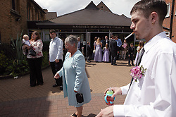 Guest smoking outside the church at a wedding,