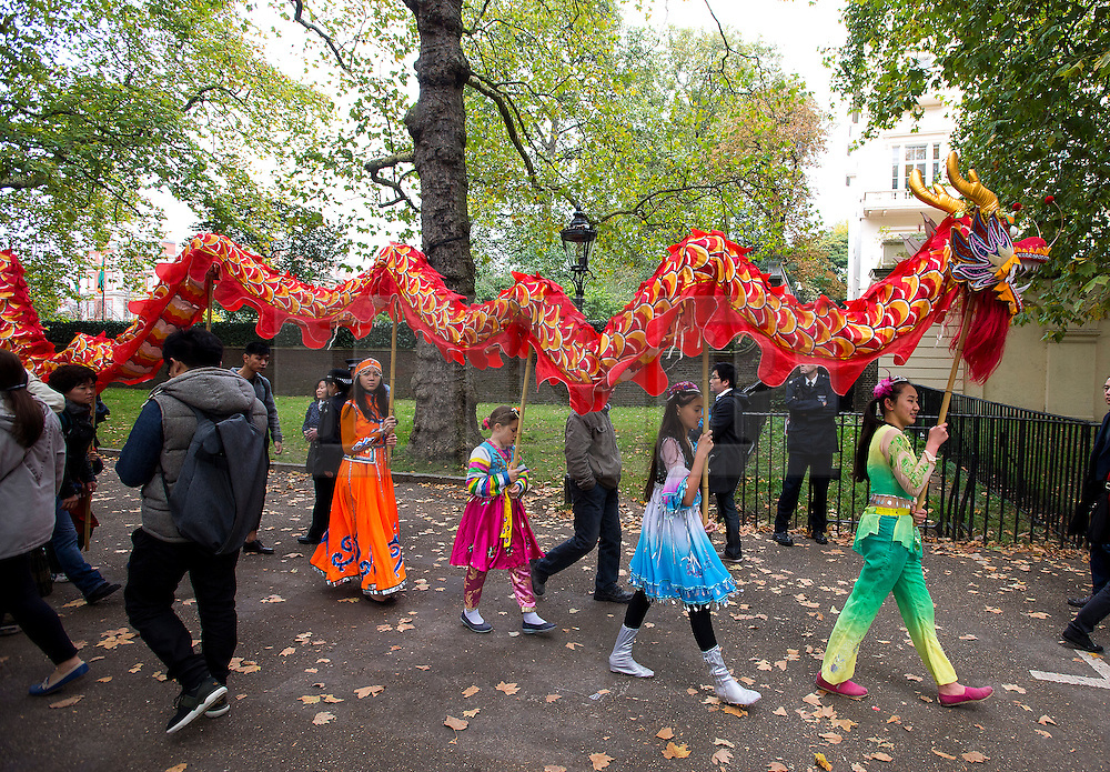 © Licensed to London News Pictures. 20/10/2015. London UK. A group of young Chinese children perform with a dragon on The Mall in London leading to Buckingham palace as Chinese President Xi Jinping starts day one of a four day State Visit to the United Kingdom. Photo credit: Ben Cawthra/LNP