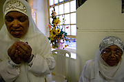 """The celebration of Mahomet birthday is an important event of the Islamic tradition. Keeping the tradition from one generation to the other, the Muslims women of Cape Town celebrate it cutting lemon and orange tree leaves that will gift to the men of the community. The particularity of the ceremony is that only the women can participate to the cutting of the leaves while the men of the community pray in one other room. The only """"men"""" that are allowed are the children that still didn't reach the puberty."""