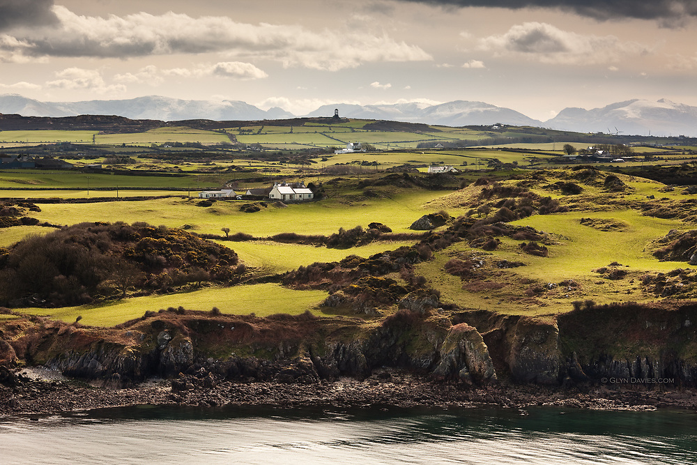 Traditional fields, white-washed roofs of Anglesey cottages, the ancient mine at Mynydd Parys in the middle distance and in the far distance, the high peaks of Tryfan and Yr Wyddfa (Snowdon).  Shot from above the brick works at Porth Wen,