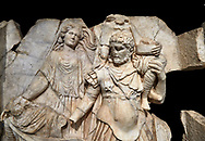 Close up of a Roman Sebasteion relief  sculpture of Aineas' flight from Troy, Aphrodisias Museum, Aphrodisias, Turkey.   Against a black background.<br /> <br /> Aineas in armour carries his aged farther Anchises on his shoulders and leads his young son Lulus by his hand. They are fleeing from the sack of Troy. The figure floating behind is Aphrodite, Aineas' mother: she is helping their escape. Old Anchises carries a round box that held images of Troy's ancestral gods. .<br /> <br /> If you prefer to buy from our ALAMY STOCK LIBRARY page at https://www.alamy.com/portfolio/paul-williams-funkystock/greco-roman-sculptures.html . Type -    Aphrodisias     - into LOWER SEARCH WITHIN GALLERY box - Refine search by adding a subject, place, background colour, museum etc.<br /> <br /> Visit our ROMAN WORLD PHOTO COLLECTIONS for more photos to download or buy as wall art prints https://funkystock.photoshelter.com/gallery-collection/The-Romans-Art-Artefacts-Antiquities-Historic-Sites-Pictures-Images/C0000r2uLJJo9_s0