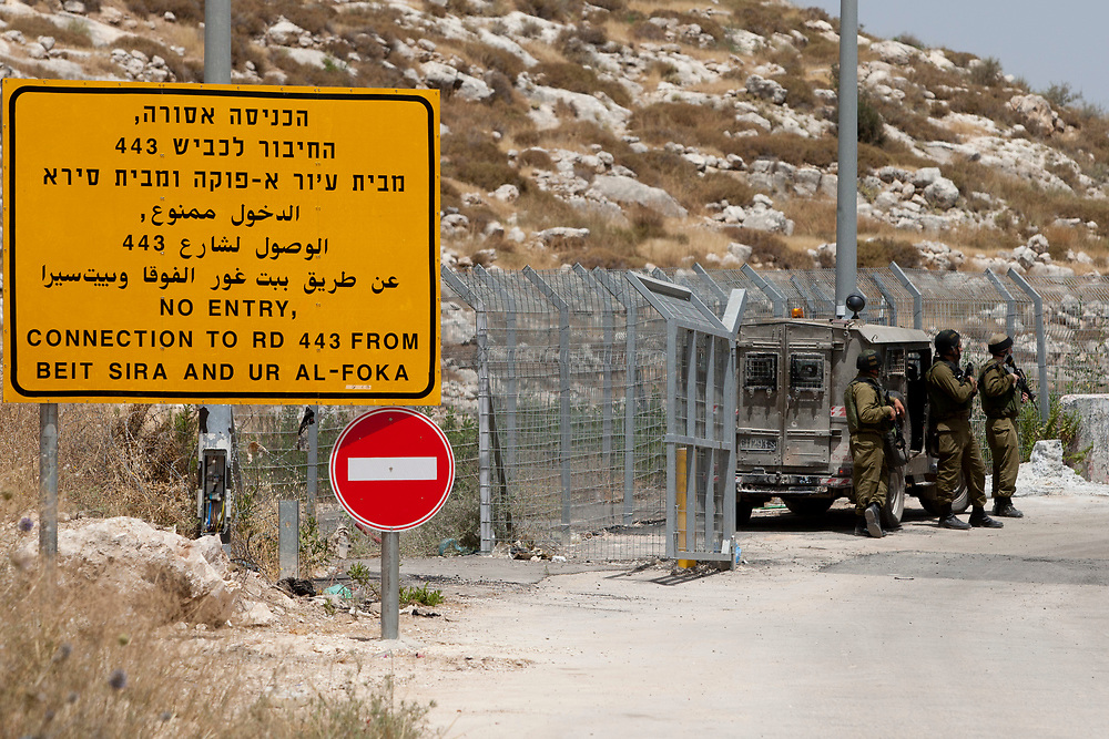 Israeli soldiers guard a new Israeli military checkpoint between the West Bank village of Beit Nuba and Road 443 where Palesinian cars are only allowed out of the highway, on June 04, 2010. The Israeli military opened part of a major West Bank highway to Palestinian cars on Friday to comply with a ruling of the country's highest court.