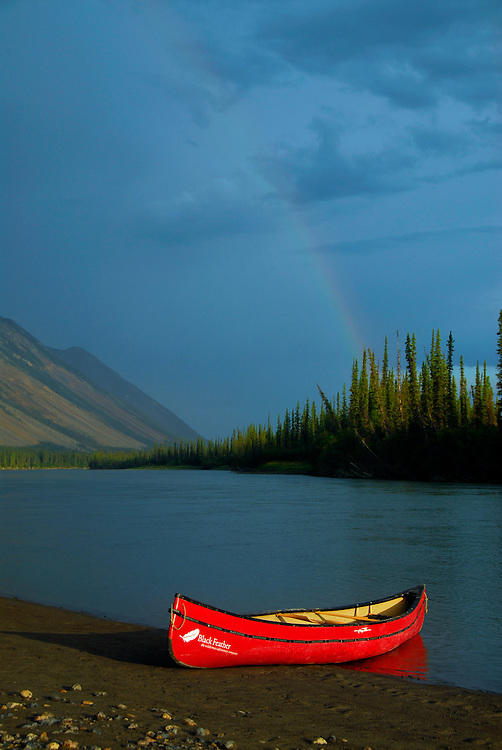 Rainbow over a canoe along the edge of the Nahanni River in Canada's Northwest Territories.