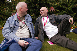 Couple of men sitting on the grass chatting at the Nottingham Pride Gay Lesbian festival; held at the Arboretum,