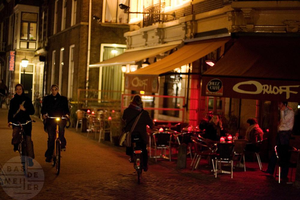 Fietsers rijden voorbij een terras aan het Wed in Utrecht waar de gasten buiten kunnen zitten in januari.