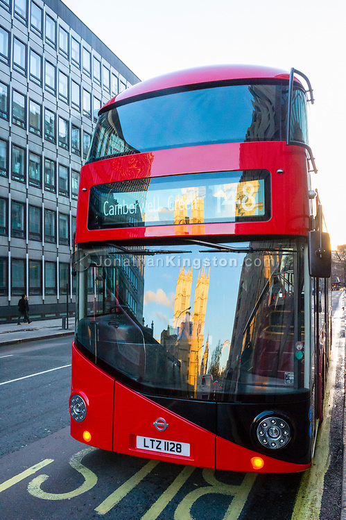 Westminster Abbey reflected in the windshield of a red double-decker bus in London, England.