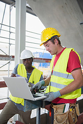Construction workers working on laptop at building site, Munich, Bavaria, Germany