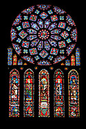 Medieval Rose Window of the North Transept of the Gothic Cathedral of Chartres, France- Circa 1235. A UNESCO World Heritage Site. The 10.5m rose window is dedicated to the Virgin Mary . The central oculus shows the Virgin and Child and is surrounded by 12 small petal-shaped windows, 4 with doves (the 'Four Gifts of the Spirit'), the rest with adoring angels carrying candlesticks. Beyond this is a ring of 12 diamond-shaped openings containing the Old Testament Kings of Judah, another ring of smaller lozenges containing the arms of France and Castille, and finally a ring of semicircles containing Old Testament Prophets holding scrolls. The presence of the arms of the French king (yellow fleurs-de-lis on a blue background) and of his mother, Blanche of Castile (yellow castles on a red background) are taken as a sign of royal patronage for this window. Beneath the rose itself are five tall lancet windows (7.5m high) showing, in the centre, the Virgin as an infant held by her mother, St Anne - the same subject as the trumeau in the portal beneath it. Flanking this lancet are four more containing Old Testament figures. Each of these standing figures is shown symbolically triumphing over an enemy depicted in the base of the lancet beneath them - David over Saul, Aaron over Pharaoh, St Anne over Synagoga, etc .<br /> <br /> Visit our MEDIEVAL ART PHOTO COLLECTIONS for more   photos  to download or buy as prints https://funkystock.photoshelter.com/gallery-collection/Medieval-Middle-Ages-Art-Artefacts-Antiquities-Pictures-Images-of/C0000YpKXiAHnG2k