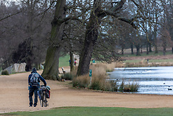 © Licensed to London News Pictures. 30/03/2020. London, UK. A man pushes his bike through a near empty Richmond Park as increased police patrols and the Government's social distancing message to say at home gets through to the wider public: As Downing Street chief aide, Dominic Cummings goes into self-isolation as the coronavirus crisis continues. Photo credit: Alex Lentati/LNP