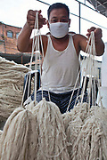 A Nepalese male factory worker holds out bundles of raw wool that he has sorted in the outdoor store area of the R.C Rug Factory in the Narayanthan area of Kathmandu, Nepal. The company export rugs and carpets to Europe the U.S and Canada, and rely on the GoodWeave certificate of approval to boast excellent quality and fair conditions for its workers, as the carpet factory industry in Nepal is notorious for providing poor working conditions and forcing young children into labour.