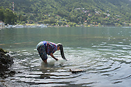 After finishing a load of laundry, Abuelita washes her hair in Lake Atitlan.