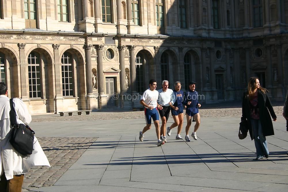 Four men jogging at the Louvre museum, Paris, France.<br />