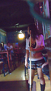 SEX INDUSTRY TOURISM. South East Asia, Cambodia, Phnom Penh. Taxi girls, prostitutes, serve foriegn tourists & Khmer, Cambodians. The sex industry is part of the fabric, servicing all classes of Cambodian society. Girls are forced into prostitution because of poverty and corruption that exists across the country. People might earn 1 to 2 $ per day, even less in rural areas, so the lure of prostitution is high. Families can sell young girls, virgins, for several hundred dollars. Cheap brothels line the streets in parts of the city centre, near railway tracks, and on the periphery. Sex for Cambodians at cheap prices in the street brothels, as low as 1 $ US, to exorbitant fees in penthouse hotel suites for the rich. Sex tourism industry attracts Western and Asian tourists typically paying 10 - 30 $ US. Expressions such as 'yam yam', eating, for a blowjob 'bam bam' for intercourse. There are 'lady-boys', youths, who use the money to pay for  sex change operations. Prostitutes spend lots of money on make-up, clothes, and mobile telephones. They live in squalor. Due to public advertising campaigns and outreach work, Aids and HIV cases have dramatically decreased, in Cambodia, since the late '90s. Condoms are encouraged, are cheap and widely available. This is seen as  a success story by medical and health authorities. There are risks as ex-prostitutes known as 'sweethearts' don't use condoms with their partners. Brothels, v & madams take their cut, but many taxi-girls work as free agents. Bars, pool halls or beer gardens have staff and taxi-girls available to service male clients, some work as barmaids or escorts. There is violence against prostitutes; gang-rape and murder by Khmer gangs. Once a girl has worked as a prostitute it is unlikely she can ever marry.///A taxi-girl, prostitute, dressed up with boots, fishnet tights and low cut t-shirt attracts customers in a pool bar.