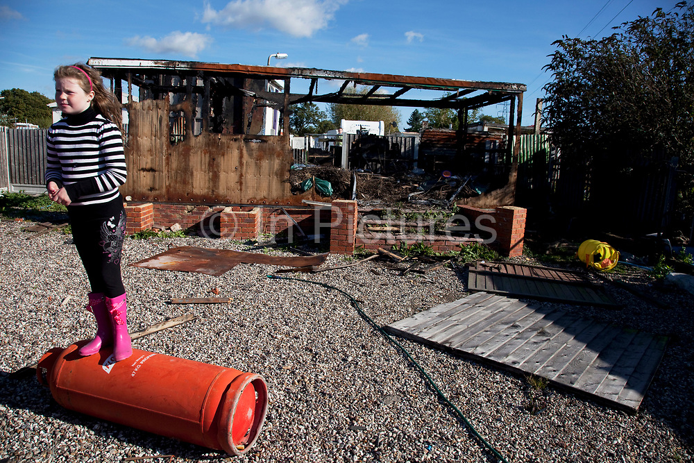 Young member of the McCarthy family plays on a gas canniester by a burned out building at Dale Farm site prior to eviction. Riot police and bailiffs were present on 20th October 2011, as the site was cleared of the last protesters chained to barricades. Dale Farm is part of a Romany Gypsy and Irish Traveller site in Crays Hill, Essex, UK. <br /> <br /> Senior resident Kathleen McCarthy said she now wished to leave, once obstacles are removed, and the majority of residents are expected to join her. Most plan to relocate to Oak Road, on the neighbouring legal site.<br /> <br /> Dale Farm housed over 1,000 people, the largest Traveller concentration in the UK. The whole of the site is owned by residents and is located within the Green Belt. It is in two parts: in one, residents constructed buildings with planning permission to do so; in the other, residents were refused planning permission due to the green belt policy, and built on the site anyway.