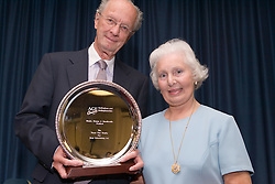 Elderly woman receiving an award for Best Entertainer at Age Concern event,