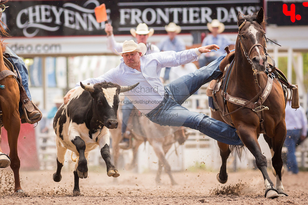 Steer Wrestler Casey Downs of Kersey, Colorado grabs the horns of a steer at the Cheyenne Frontier Days rodeo at Frontier Park Arena July 24, 2015 in Cheyenne, Wyoming. Frontier Days celebrates the cowboy traditions of the west with a rodeo, parade and fair.
