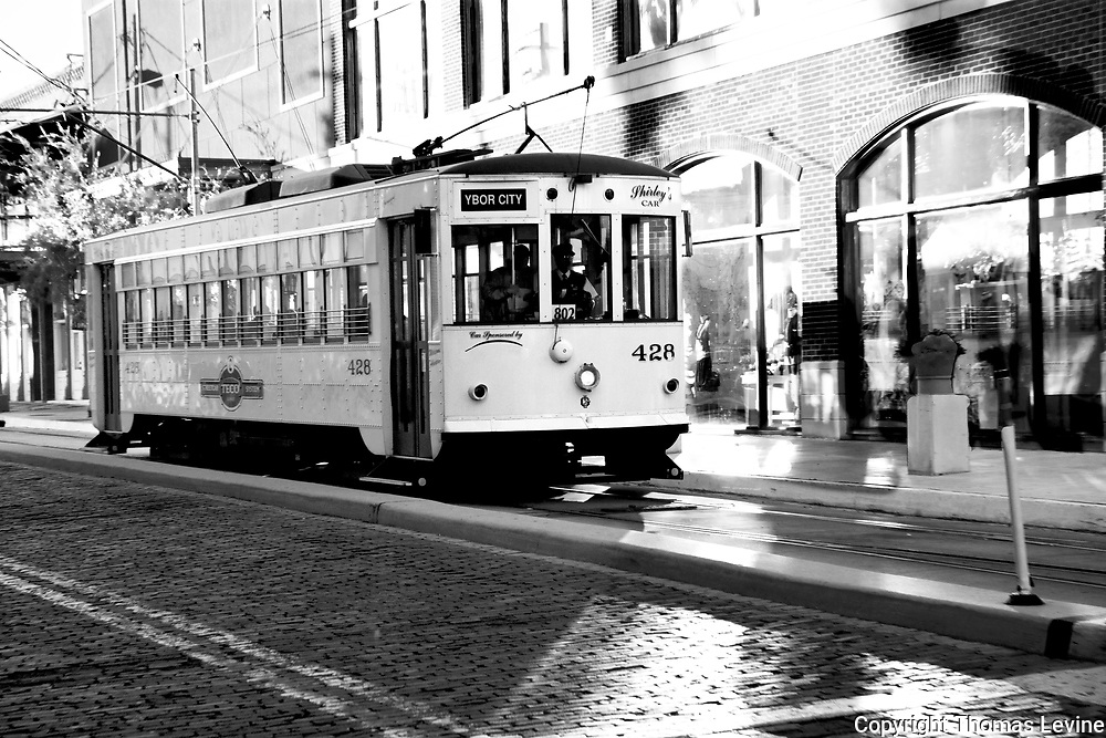 Dec. 2005, Tampa, Florida: Electric Street Car trolly going down an old brick street in Ybor City. High Key Light on the brick building behind the street car. Black & White, RAW to Jpg