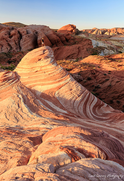 A lone hiker stands atop the Fire Wave in Valley of Fire State Park, Nevada, in early morning light.