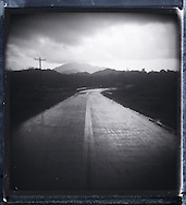Picture of a curved road going throught countryside.  Stormy weather brings dark atmosphere to the photograph. Palawan island, Philippines, Asia.